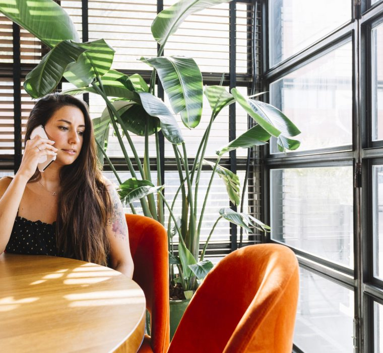 beautiful-young-woman-sitting-in-restaurant-talking-on-mobile-phone
